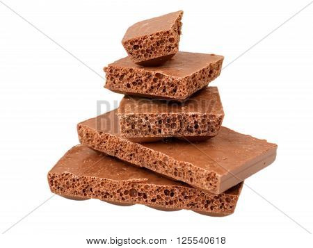 Stack of pieces of porous milk chocolate isolated on white