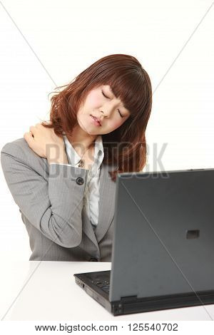 Japanese businesswoman suffers from neck ache on white background