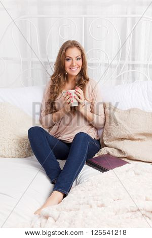 Pretty woman relaxing in the bed with a cup of hot drink
