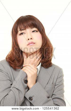 studio shot of young Japanese businesswoman having throat pain