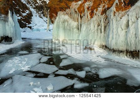 White ice floes in transparent and frost on the rocks. Beautiful winter landscape in the Lake Baikal.