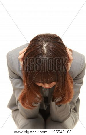 studio shot of young Japanese businesswoman cries