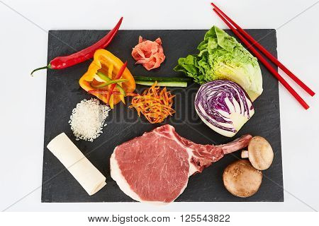 Raw steak served with vegetables and forest mushrooms on black metal cutting board