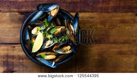 Mussels in clay bowl and lemon on wooden dark background