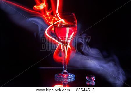 Glass of wine and red light painting with smoke on the black background