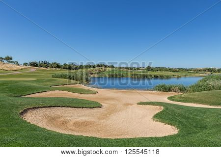 Sand trap on the golf course with a lake. Panorama landscape.