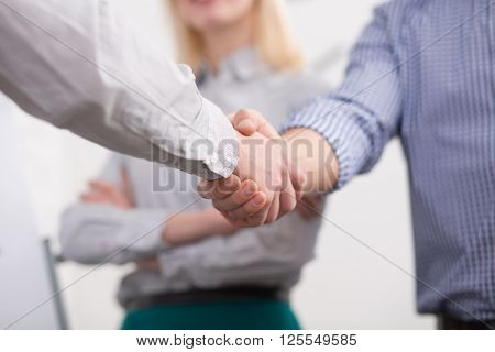 Business handshake concept. Business people are handshaking during meeting in office. Handshake in front of business lady.