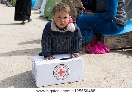 EIDOMENI, GREECE - MARCH 17, 2015: A little boy tries to carry a box with supplies on March 17, 2015 in the refugees camp of Eidomeni, Greece. For several weeks more than 10.000 refugees and immigrants wait here for the borders to open.