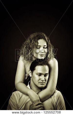Redhead girl hugging her boyfriend over dark background