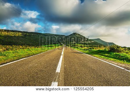 country road under huge clouds in Sardinia Italy
