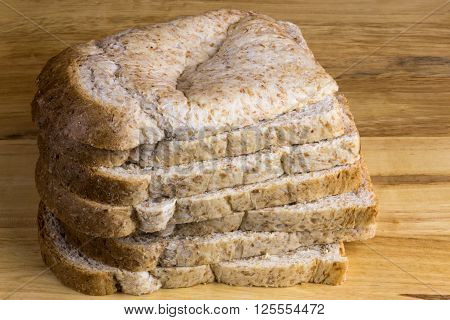 Stack of wholemeal bread slices on a wooden bread board