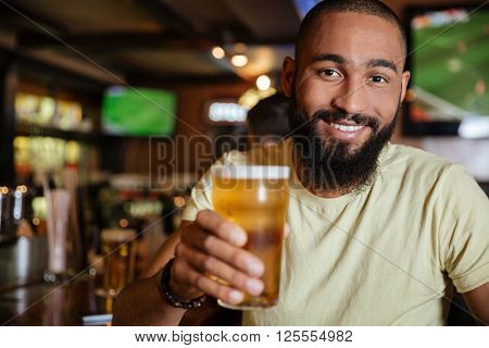 Cheerful attractive african american young man drinking beer in pub