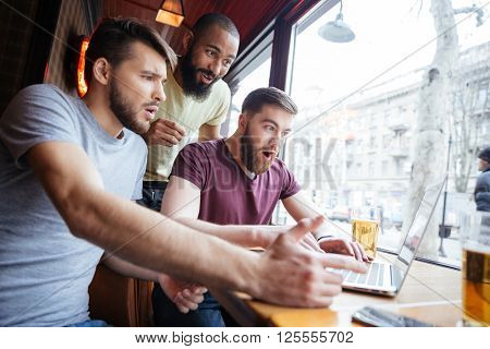 Three amazed shocked handsome men watching video on laptop together and shouting in cafe
