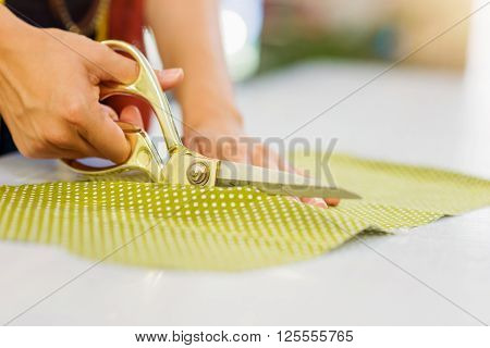 Close up of hands of unrecognizable tailor woman cutting green dotted fabric with scissors