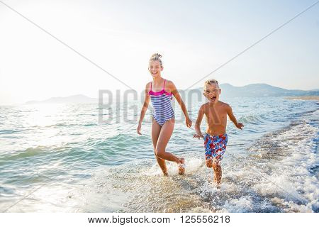 Happy brother and sister running at tropical beach against sunlight