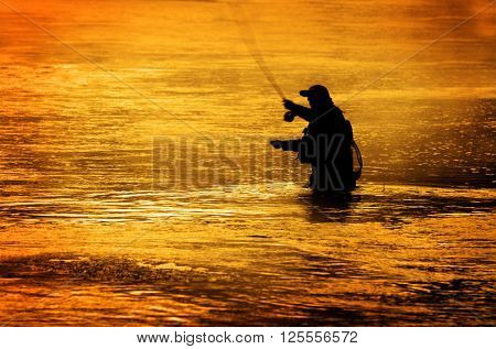 Man fishing in river or lake silhouette by sunrise and misty water
