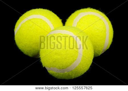 Three lawn tennis balls close-up on a black background