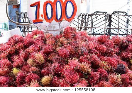 Pile of rambutan fruits with a price tag sold at a local fresh market in San Jose Costa Rica