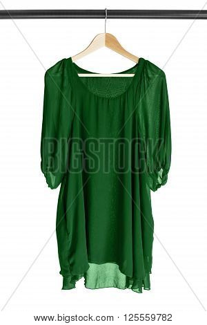Green chiffon dress hanging on clothes rack isolated over white