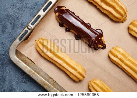 Eclairs or profiteroles with chocolate and whipped cream preparing on baking sheet background. Traditional homemade French cuisine dessert. Top view