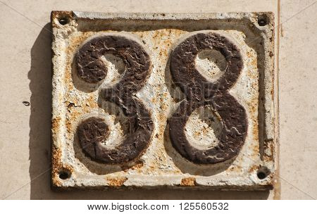 Old retro weathered cast iron plate with number 38