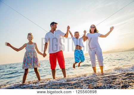 Family of four having fun at the beach. Sunset time.