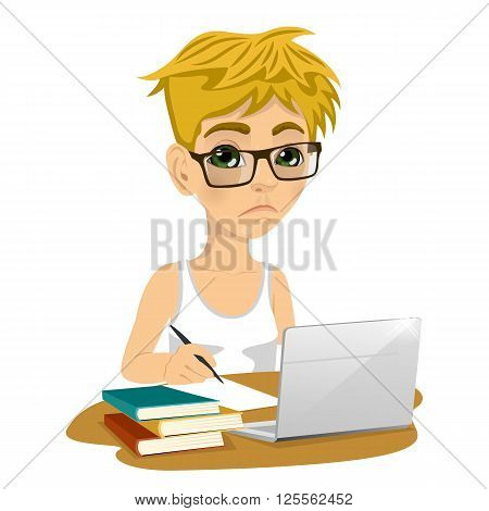 Unhappy teenage schoolboy with glasses doing his homework with laptop and books on desk isolated on white background