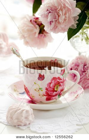 A cup of black tea,sweets and peonies