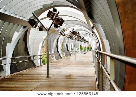 Fantastic view on a metal walking bridge over the Park in Madrid. Spain. Architectural details.