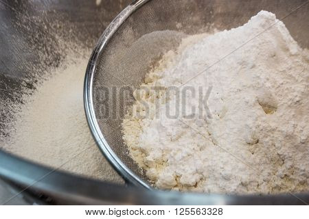 close up powder sugar in a metal sieve on metal