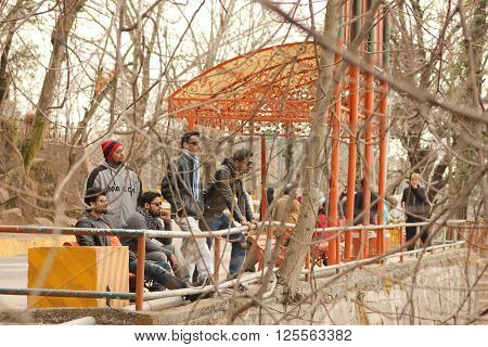 Murree, Punjab, Pakistan - Jan 07,  2014 - A Group of Tourists standing on a hill side and watching down the mountains.
