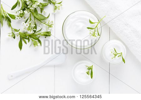 Herbal dermatology cosmetic hygienic cream with flowers skincare product in glass jar on white background