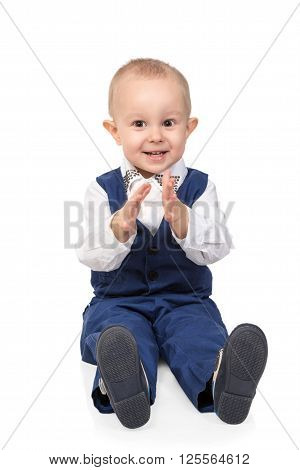 Cheerful boy in a blue suit sitting on the floor and clapping isolated on white background