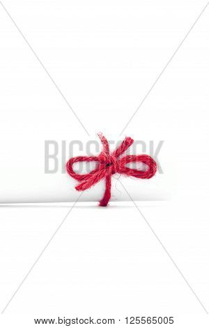 Handmade red cord node tied on white letter roll isolated
