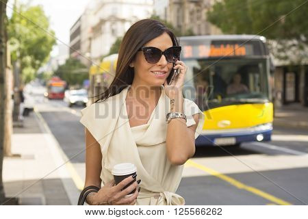 Fashionable young brunette wearing white dress and sunglasses laughs into phone on street city urban space