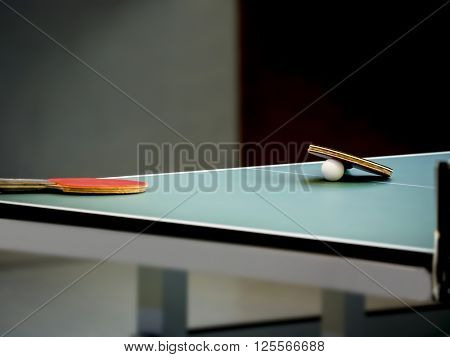 Table Tennis rackets and ball on a green Table - Focus at the right Racket/Blade and the ball, shallow DOF