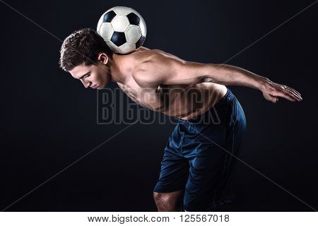 Attractive and muscular football player. Studio shot of young shirtless sportsman on black background. Man with football ball on back