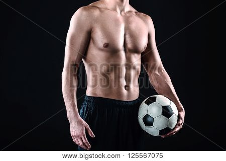 Close up of attractive and muscular football player. Studio shot of young shirtless sportsman on black background. Man with football ball