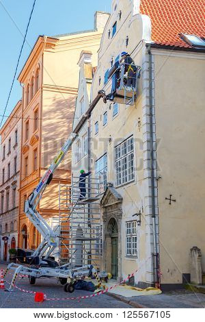 Riga, Latvia - 15 October, 2015: Working with the lifting device being restored facade of the old building. The historic center of Riga attracts many tourists.