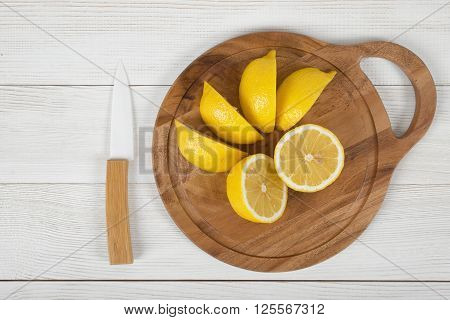 A whole and sliced lemons on cutting board with a ceramic knife next to them in top view. Food design.