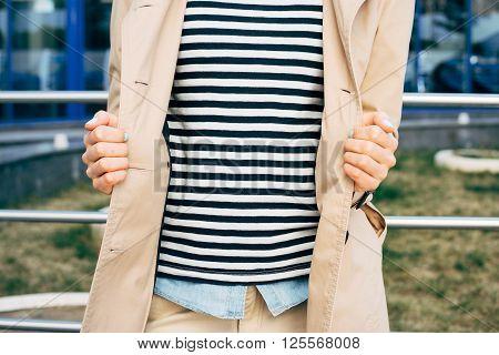 Woman In A Striped T-shirt, Denim Shirt And An Unbuttoned Beige Coat Outdoors
