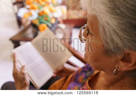Old people in geriatric hospice: senior woman with eyeglasses and miopia problems sitting on chair and reading a book.