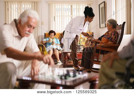 Old people in geriatric hospice: Black doctor visiting an aged patient measuring blood pressure of a senior woman. Group of retired men in foreground playing chess.