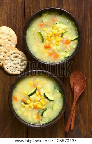 Vegetarian corn and courgette chowder served in two rustic bowls saltine crackers and wooden spoons on the side photographed overhead on dark wood with natural light (Selective Focus Focus on the top of the soup)