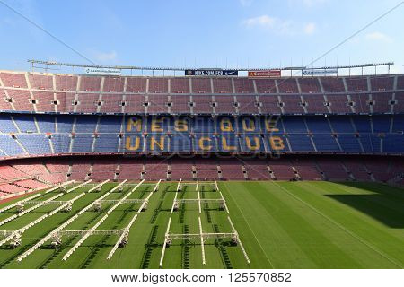 Barcelona, Spain - November 12, 2015: Football stadium Camp Nou interior with grass field, grow lighting and stands. The stadium has been the home of FC Barcelona since its completion in 1957.