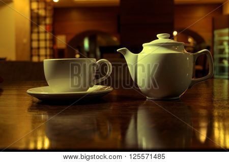 Tea time. White teacup and teapot on the wooden table in dark room, side view, toned image, colorized shot