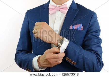 Man in blue suit with pink bow tie flower brooch and pink blue strip pocket square close up
