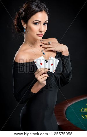 sexy woman with poker cards. Female player in a beautiful black dress. girl stands near the poker table and holds two aces