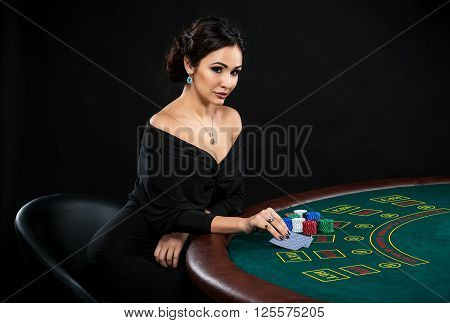 sexy woman with poker cards and chips. Female player in a beautiful black dress. girl sitting at the poker table