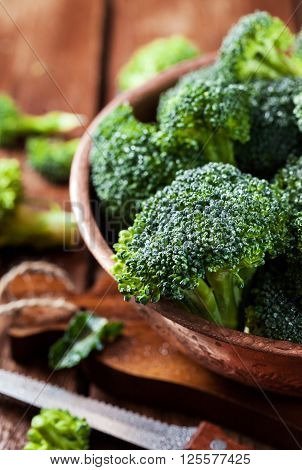 Fresh raw green broccoli in bowl on rustic wooden background ** Note: Visible grain at 100%, best at smaller sizes